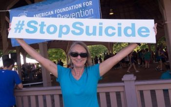 Carleen Schmittendorf, of Rochester, poses with a sign before the start of the annual Out of the Darkness Community Walk Sept. 24 at Genesee Valley Park in Rochester.
