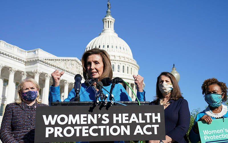 """As masked women stand in the background, an elderly woman with clenched fists raised in the air speaks into microphones attached to a podium bearing a """"Women's Health Protection Act"""" sign. House Speaker Nancy Pelosi (D-Calif.) speaks during a news conference on Capitol Hill in Washington Sept. 24 about the Women's Health Protection Act, which establishes a legal right to abortion in all 50 states under federal law. The measure passed in a 218-211 vote. (CNS photo by Kevin Lamarque/Reuters)"""