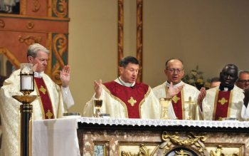 Several men in clerical garb raise their hands as they stand behind an altar. Nashville Bishop J. Mark Spalding celebrates Mass Oct. 5 at the Pastoral Center in Nashville during the 2021 Diocesan Fiscal Management Conference. During the conference, Los Angeles Archbishop Jose Gomez, president of the U.S. Conference of Catholic Bishops, said that eucharistic revival is the key to the church's future. (CNS photo by Andy Telli)
