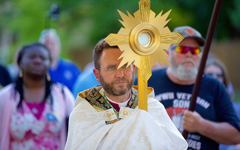 """Auxiliary Bishop Andrew H. Cozzens of St. Paul and Minneapolis carries a monstrance holding the Eucharist during a procession June 19, 2021, called """"Catholic Father's Day."""" Bishop Cozzens is chairman of the U.S. Conference of Catholic Bishops' Committee on Evangelization and Catechesis. (CNS photo by Dave Hrbacek/The Catholic Spirit)"""