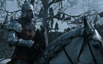 """A knight carrying a shield is riding a horse. Matt Damon stars in a scene from the movie """"The Last Duel."""" (CNS photo/20th Century Studios via EPK TV)"""