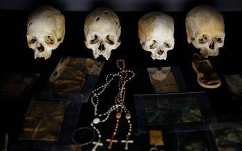 Skulls and rosaries from the Rwandan genocide are seen at a memorial. Skulls, rosaries and personal items of victims of the Rwandan genocide are pictured as part of a display at the Genocide Memorial in Kigali in 2019. More than 27 years after the ethnic genocide in which some church leaders were found complicit, Catholic leaders in Rwanda have intensified a campaign to reconcile Hutus and Tutsis. (CNS photo by Baz Ratner/Reuters)