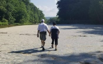 A couple holds hands while walking near trees and water. A couple holds hands while walking near trees and water.