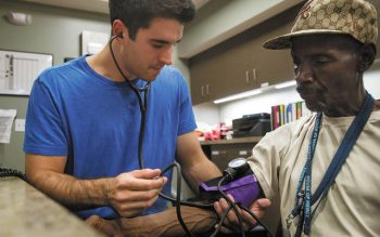 University of Rochester student Stephen Hassig takes the blood pressure of Hubert Wilkenson, a security member at the House of Mercy.