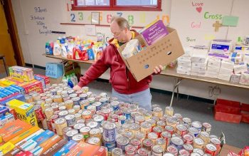 Mark Messmer loads a Christmas basket with supplies for a needy family at Rochester's Peace of Christ Parish Dec. 12, 2015.
