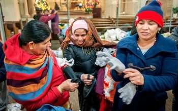 Bhutanese women try on donated gloves Dec. 9, 2013, at Mary's Place, a refugee outreach center in Rochester.