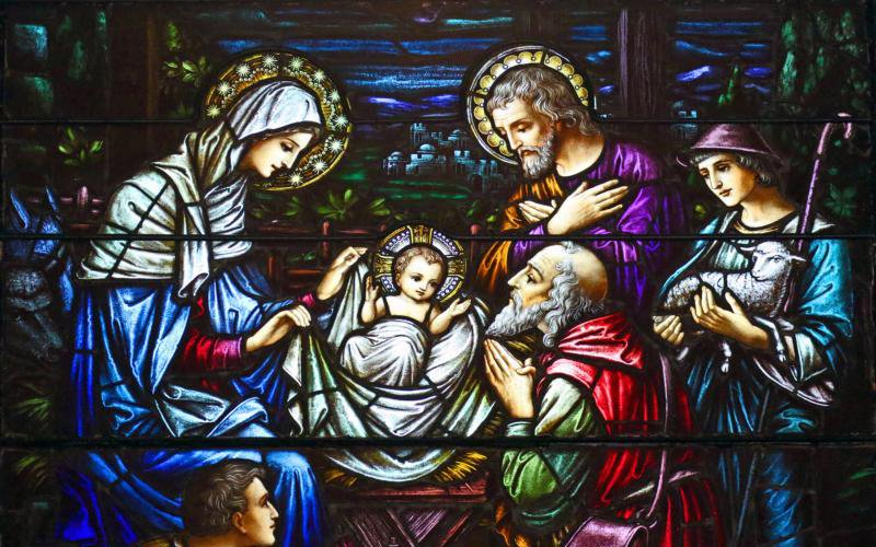 This stained-glass window at St. Aloysius Church in Great Neck, N.Y., depicts Jesus in a manger surrounded by Mary, Joseph and three shepherds. The feast of the Nativity of Christ, a holy day of obligation, is celebrated Dec. 25. (CNS photo by Gregory A. Shemitz)