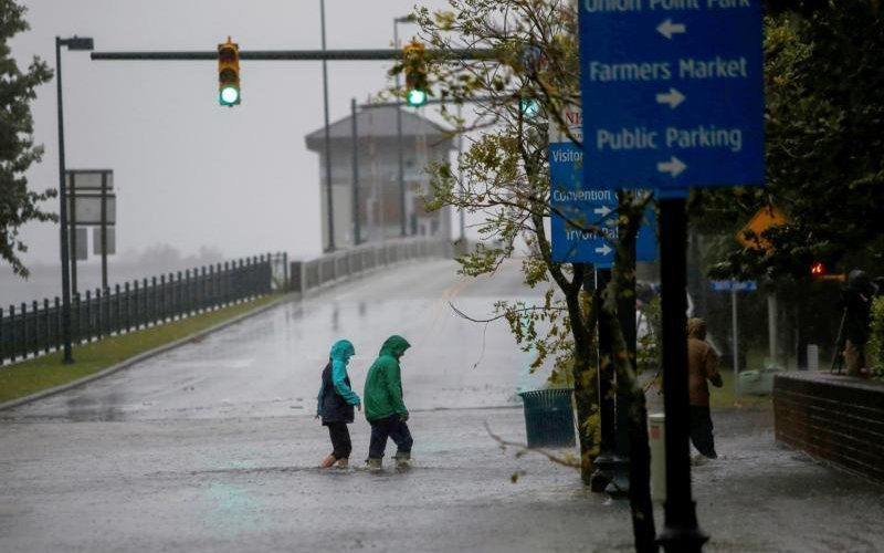 People walk on a local street in New Bern, N.C., Sept. 14 as water from Neuse River starts flooding houses ahead of Hurricane Florence making landfall in the Carolinas. The hurricane is poised to affect more than 10 million people in the southeastern U.S. (CNS photo by Eduardo Munoz/Reuters)