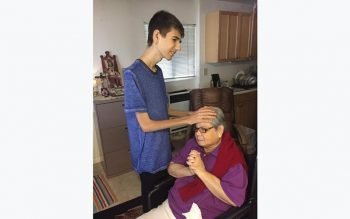 """Nicholas Peters, suffering from terminal cancer, lays hands on a woman named """"Frisca,"""" a homebound parishioner of St. Charles Parish in San Carlos, Calif.  (CNS photo courtesy Peters family)"""