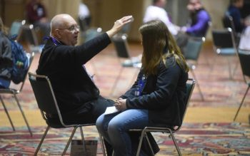Father John Hall, pastor of St. Anne Parish in New Castle, Ind., and St. Elizabeth of Hungary Parish in Cambridge City, blesses a young woman during confession Nov. 22, 2019, during the National Catholic Youth Conference in Indianapolis.