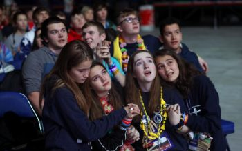 Claire Lander, Valerie Manczack, Mikaela Engstrom and Hannah Reale kneel together in prayer during the closing Mass Nov. 23, 2019, at the National Catholic Youth Conference in Indianapolis. (CNS photo/Karen Bonar, The Register) See stories marked NCYC- Nov. 22 and 25, 2019.