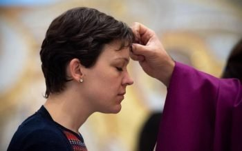A woman receives ashes during Ash Wednesday Mass at the St. John Paul II National Shrine in Washington Feb. 26, 2020.