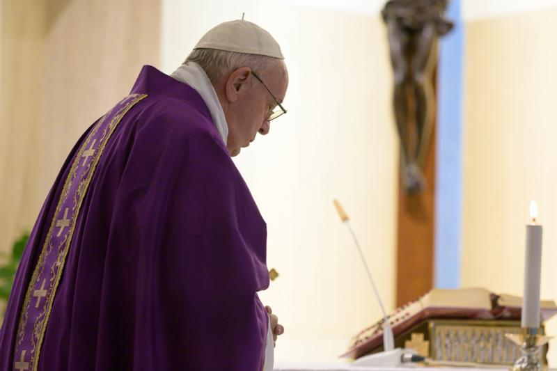 Pope Francis prays during his morning Mass March 23, 2020, in the chapel of the Domus Sanctae Marthae at the Vatican.