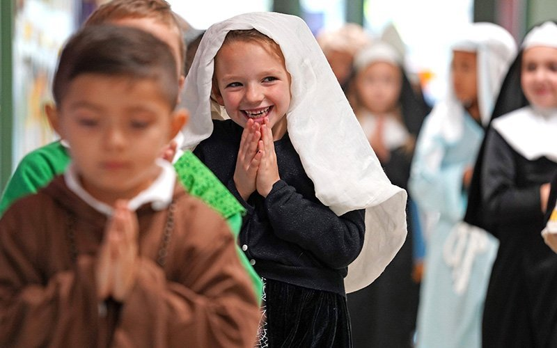 First-grader Angelina Wuerz, dressed as St. Angela, giggles as she and her classmates at St. Patrick School in Smithtown, N.Y., process from the school to an All Saints' Day Mass in the parish church Nov. 1, 2019.