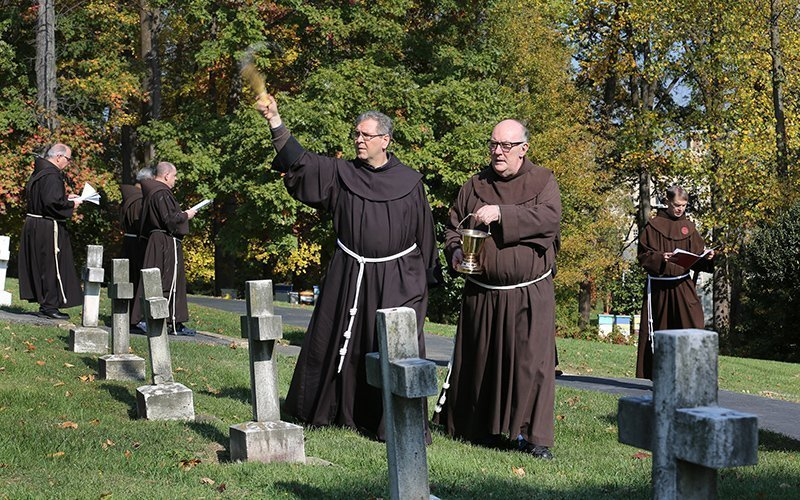 Franciscan Father Francesco Patton, the custos of the Holy Land Franciscans, sprinkles holy water on tombstones in the cemetery Nov. 2, 2016, at the Franciscan Monastery of the Holy Land in Washington to mark All Souls' Day.