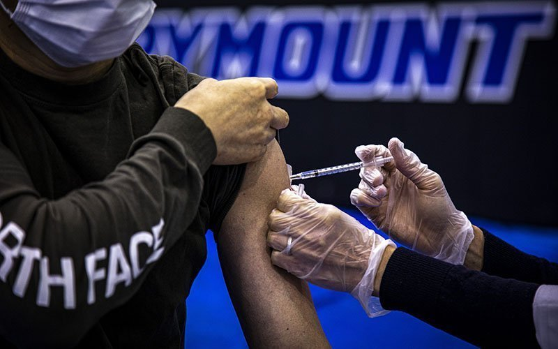A health care worker administers the Pfizer COVID-19 vaccine to a Marymount University student in one of the athletic buildings on the Catholic college's Arlington, Va., campus, during a coronavirus vaccine clinic April 21, 2021.
