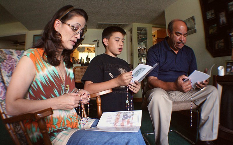 A family prays the rosary in 2012 in their Phoenix home. Parenthood always is a work in process. There always seems to be something more and something genuinely important for parents to consider in raising children. (CNS photo/J.D. Long-Garcia)
