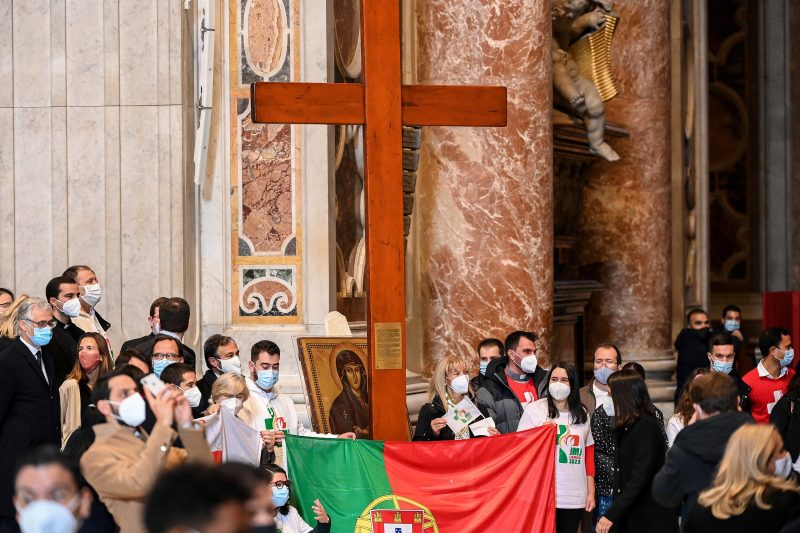 """Young people from Portugal are pictured with the World Youth Day cross and their country's national flag following the cross' handover from their Panamanian peers at the end of Pope Francis' Mass Nov. 22, 2020. Pope Francis chose several verses that reflect on the call to """"arise"""" and """"stand up"""" as the themes for World Youth Day 2020-2022 in dioceses around the world, leading up to the international gathering in Lisbon, Portugal, in 2023. (CNS photo/Vincenzo Pinto, Reuters pool)"""