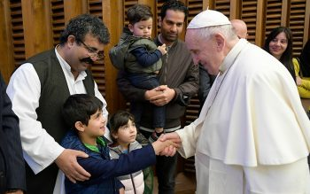 Pope Francis greets a child as he meets families who fled from Afghanistan, during his general audience in the Paul VI hall at the Vatican Oct. 13, 2021.