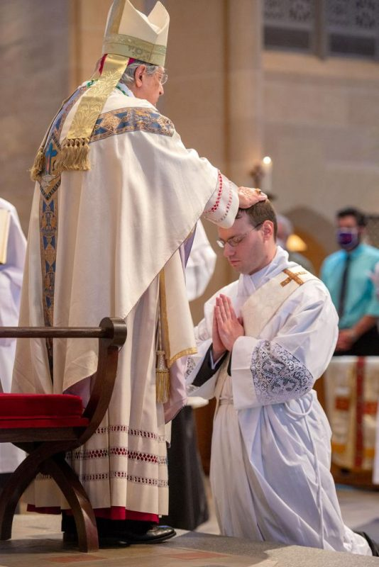 Bishop Matano places his hands on the head of Father Maurici.