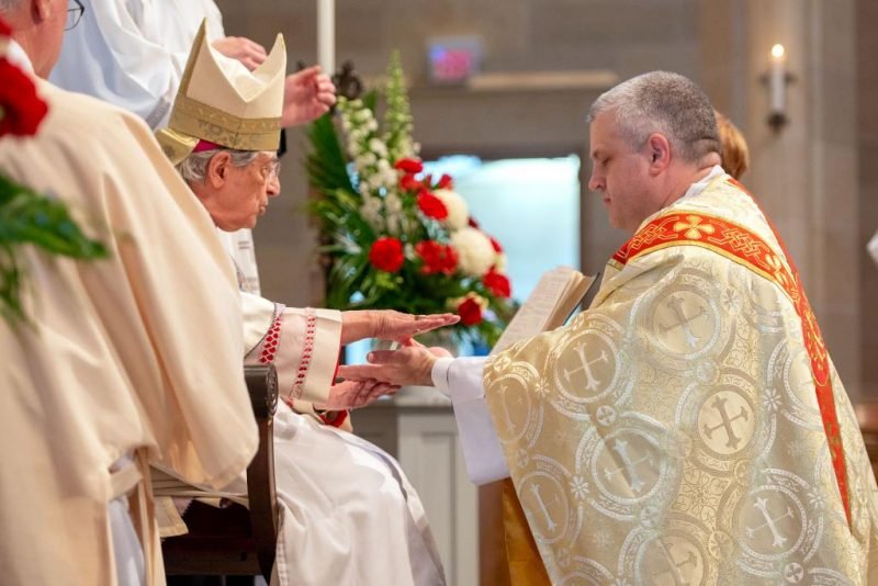 Bishop Matano anoints the hands of Father Lewis.