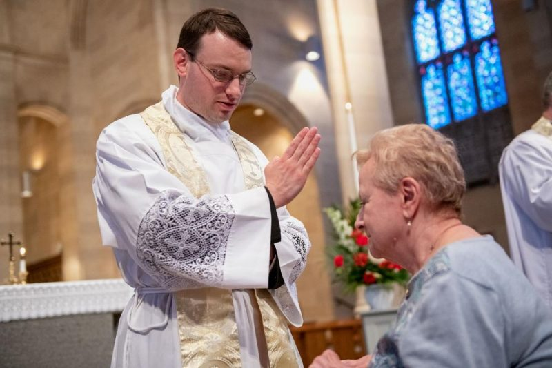Elaine Nazzaro receives a blessing from Father Maurici following the Mass.