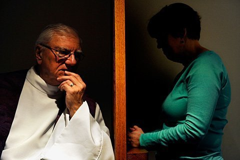 Although face-to-face confession has been an option since the 1970s, Catholics may still opt to receive the sacrament of rec-onciliation with a grill separating them from the priest. Above, Father Ed Palumbos demonstrates this form of the sacrament atFairport's Church of the Assumption.