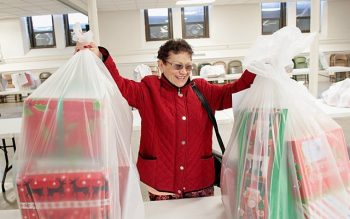 Luz Figueroa picks up two baskets with Christmas gifts for her and her family Dec. 20 at Our Lady of the Americas Church in Rochester. Each year St. Frances Xavier Cabrini Parish uses a grant that includes Christmas Appeal funds to purchase Thanksgiving and Christmas baskets for needy community members.