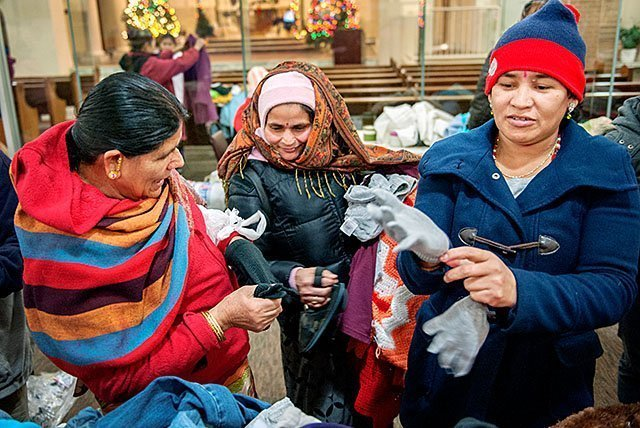 Bhutanese women try on donated gloves Dec. 9 at Mary's Place, a refugee outreach center in Rochester.