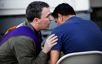 Father Mickey McGrath (left) hears a confession during the Santa Misionat Rochester's Holy Apostles Church in 2011.