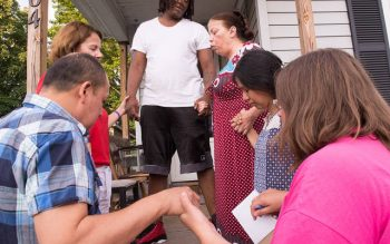 """Members of a """"Missionaries of Peace"""" team from Rochester's Holy Apostles Church pray with a neighbor Aug. 2. (Courier photo by John Haeger)"""