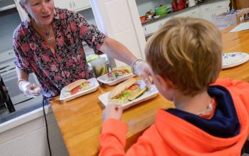 Mary Margaret Loman serves a sub sandwich to a student at St. Francis-St. Stephen School in Geneva Sept. 20. (Courier photo by John Haeger)