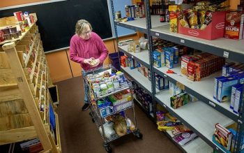 Volunteer Mary O'Grady-Pero pulls items from shelves at the Spencerport Ecumenical Food Shelf Nov. 29. (Courier photo by Jeff Witherow)