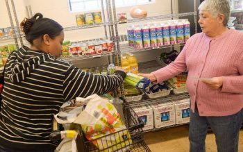 Perdomo Carmen (right) helps Tammy Liddell as she receives food at the Sister Regis Food Cupboard Nov. 19 in Rochester. (Courier photo by John Haeger)