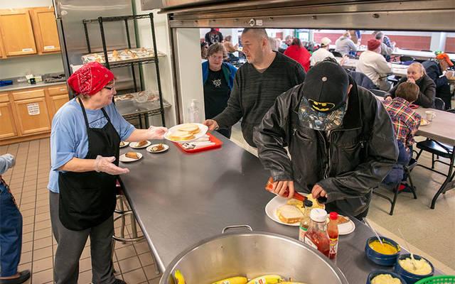 Sharon Birdsall serves meals at Elmira Community Kitchen March 14.