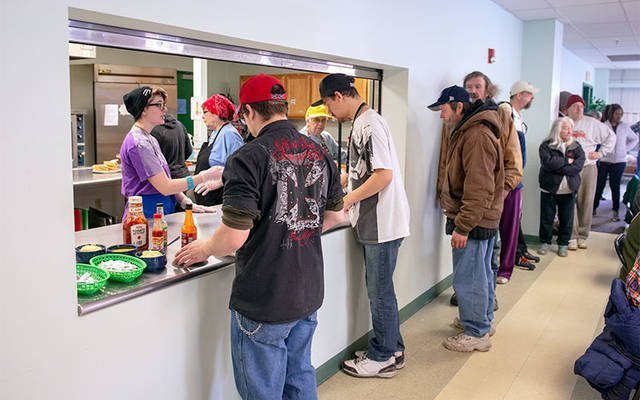 Patrons of Elmira Community Kitchen stand in line to receive meals during a March 14 lunch.