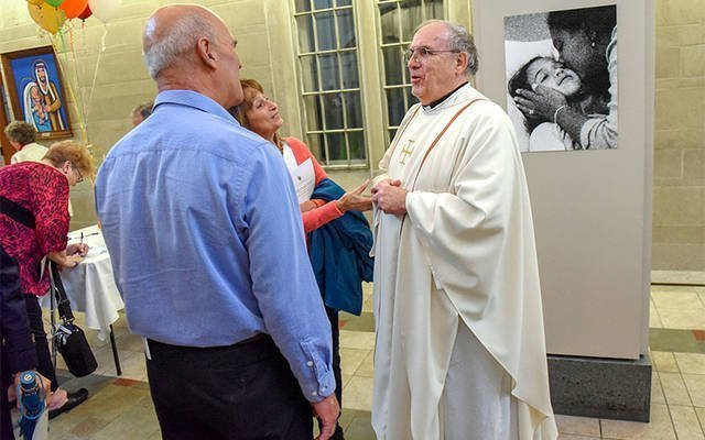 Tom and Annette Basset greet Father James Hewes during a reception following the 2016 Diocesan Respect Life Mass at Sacred Heart Cathedral. Father Hewes was honored for his commitment to Project Rachel. (Courier file photo)