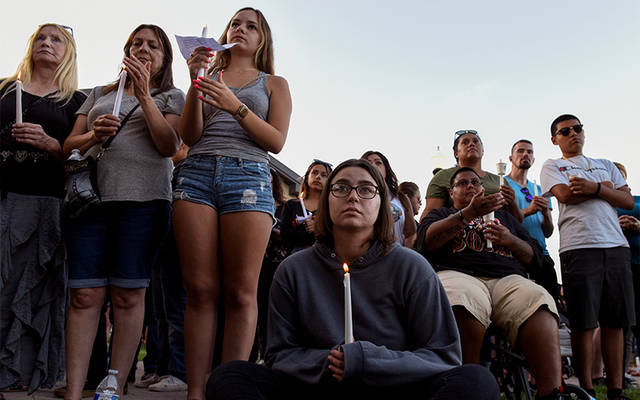 People attend a candlelight vigil outside Gilroy City Hall in California July 29 to honor those that died and were injured during a mass shooting at the Gilroy Garlic Festival a day earlier. The Diocese of San Jose held a bilingual prayer vigil July 29 for victims, survivors and first responders at St. Mary Church in Gilroy. (CNS photo by Kate Munsch/Reuters)