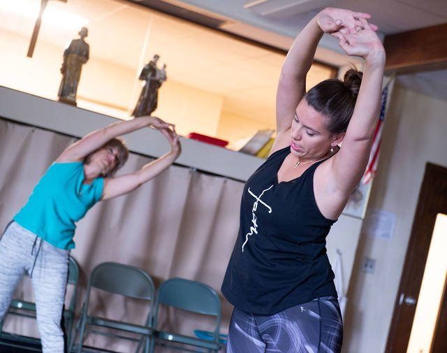 Kristen Muir leads a SoulCore class in the parish hall at St. Leo Church in Hilton Aug. 18. The core-strengthening workout centers around praying the rosary and reflecting on its virtues.