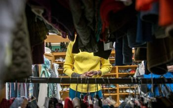 Esperence Batamuriza goes through racks of clothing Oct. 18, 2017, at the Saint's Place clothing closet, located at St. John of Rochester Church in Fairport. (File photo)