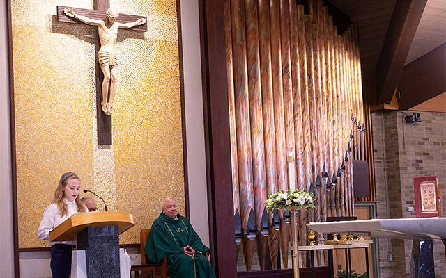 Cora Schickley, a student at St. Joseph School in Penfield, proclaims the first reading during a Catholic Schools Week Mass Jan. 26 at St. Joseph Church. As part of the school's focus on social and emotional learning, students are encouraged to take on liturgical roles during school Masses. (Courier photo by John Haeger)