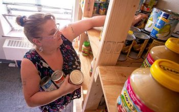 Brenda Hartmetz pulls items from the shelves Aug. 10, 2016, at Joseph's Place, a food pantry operated by Rochester's Cathedral Community. (File photo)