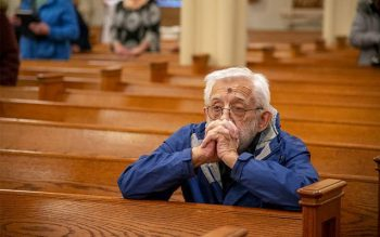 Bob Westfall kneels in prayer after receiving ashes during an Ash Wednesday liturgy at St. Agnes Church in Avon Feb. 26. (Courier photo by Jeff Witherow)