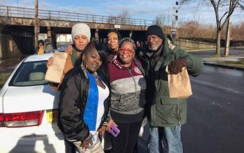 Participants in Family Independence Initiative Rochester hand out food and personal-hygiene supplies at Rochester's House of Mercy. (Photo courtesy of Latanya Banks)
