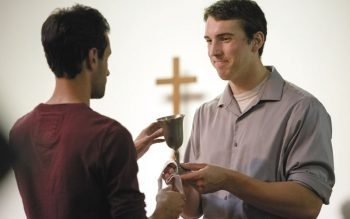 David Pollock serves as an extraordinary minister of holy communion during Mass at SUNY Geneseo's Interfaith Center in 2014.