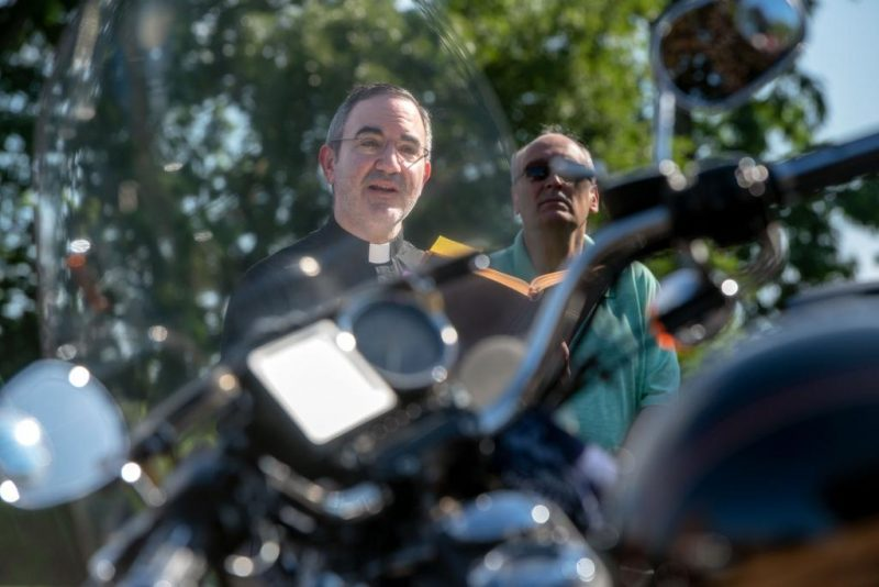 Father William Coffas speaks during the bike blessing.