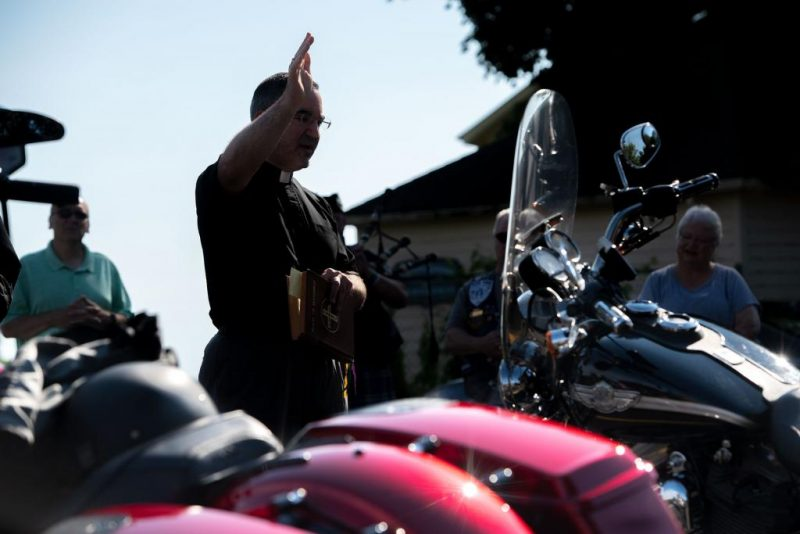 Father William Coffas raises his hand to bless the motorcycles.