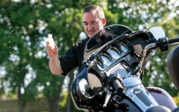 Father William Coffas sprinkles the motorcycles with holy water.