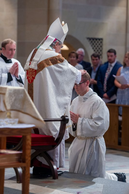 Bishop Matano places his hands on Aaron Kelly's head.