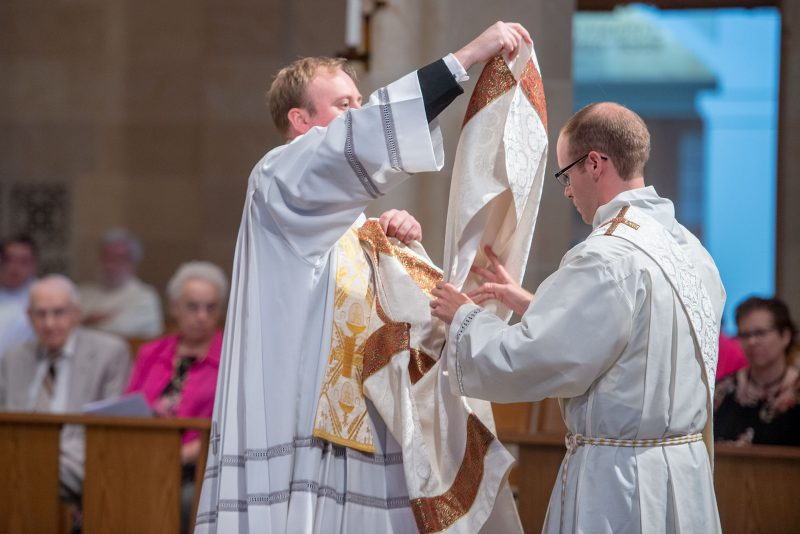 Deacon Aaron Kelly is vested by Father Peter Van Lieshout.